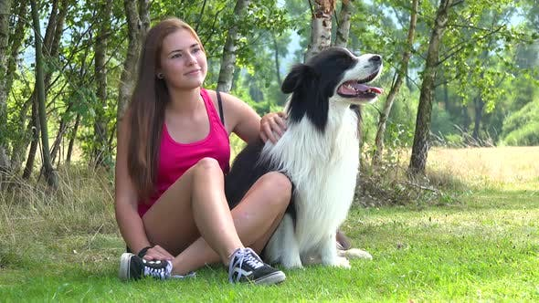 Thumbnail for A Young Beautiful Woman and a Border Collie Sit in a Meadow, the Woman Pets the Dog and Looks