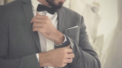Man in Formal Suit Getting Dressed in Dressing Room for Work or Wedding