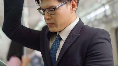 Businessman Using Mobile Phone on Public Train