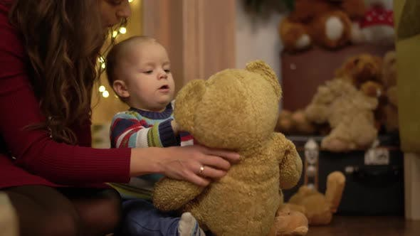 Cover Image for Little Cute Child Playing with Big Teddy Bear at Home