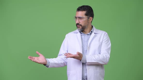 Handsome Persian Bearded Man Doctor Wearing Protective Glasses and Showing Something