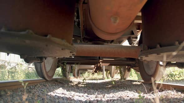 Thumbnail for Dolly Video of Cameray Moving Under Old Rusty Cargo Train Car on Abandoned Railrod. Concept of