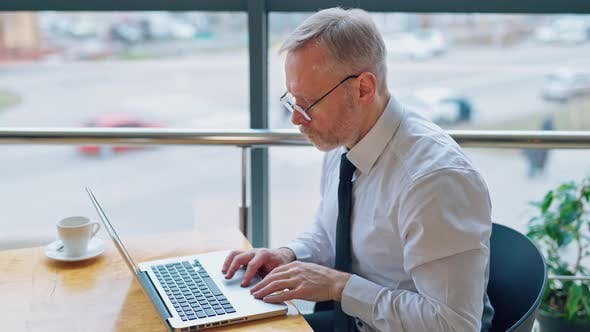 Thumbnail for Serious businessman typing on a computer indoors on city background