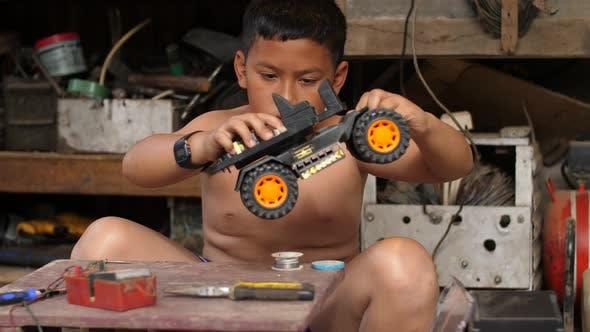 Boy Testing Car Toy After Repair