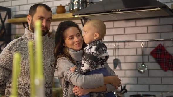 Thumbnail for Bearded Father in Warm Sweater Playing with Baby Little Son Who Is in Mother Arms in the Kitchen