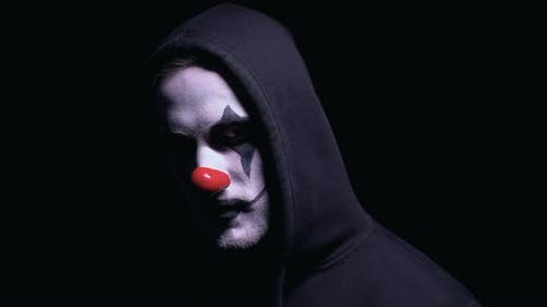 Crazy Clown Man With Gun Ominously Looking Into Camera, Murderer Threatening