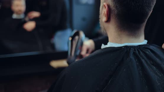 Hairdresser Blows Off Hair From the Client's Cape