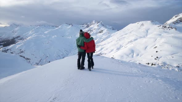 Thumbnail for A man and woman couple standing on top of a mountain lifestyle in the snow winter