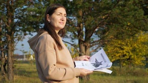 Upset Woman in Hoodie Looks at Missing Cat Posters in Park