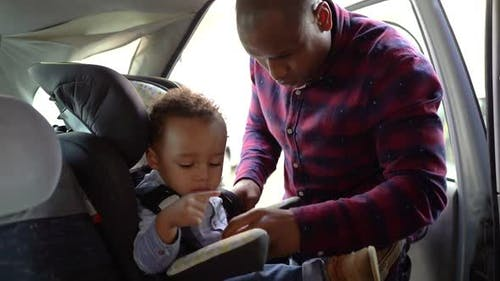 African American Bald Dad Checking Belts on Child Car Seat