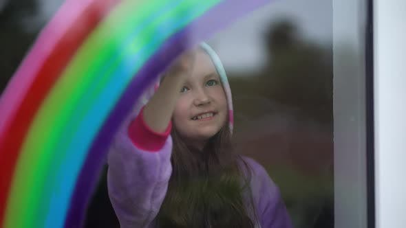 Stay Home, Flash Mob Chase the Rainbow. Girl in Pajamas Draws the Rainbow on the Window at Home