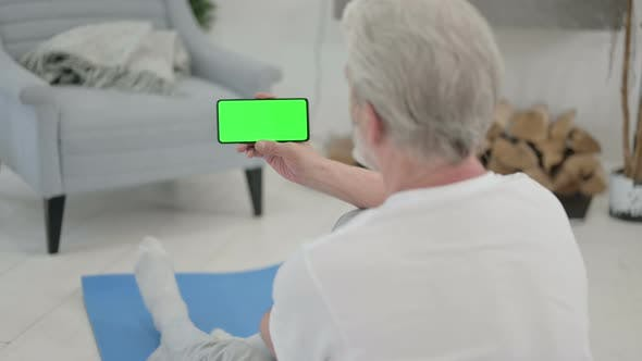 Rear View of Old Man Looking at Smartphone with Chroma Key Screen on Yoga Mat
