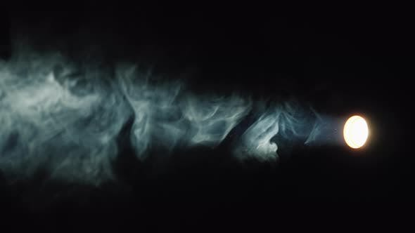 A Flashlight Beam Illuminates the Smoke on a Black Background