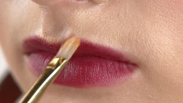 Make-up Artist Making Lips Contour, Beautiful Woman with Vinous Lipstick and Yellow, Close Up, Slow