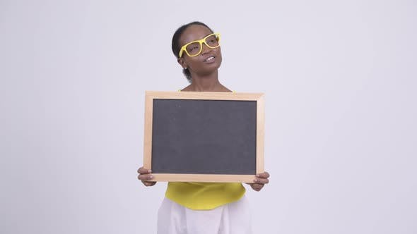 Thumbnail for Happy Young Beautiful African Woman Holding Blackboard and Thinking
