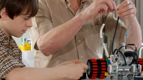 Thumbnail for Senior Man and His Grandson Assembling Toy Vehicle