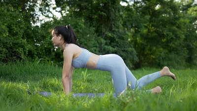 Asian woman practicing pilates with earphone