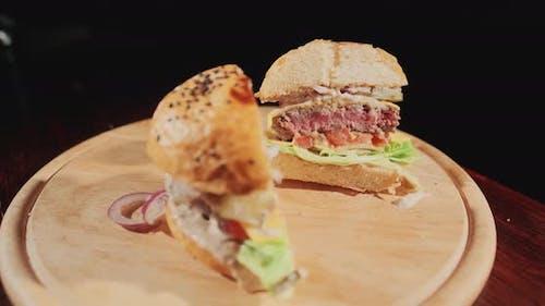 Appetitanregende frische saftige gekochte Burger in einem Schnitt. Sehr üppiges Luftbrötchen und marmoriertes Rindfleisch mit Sauce