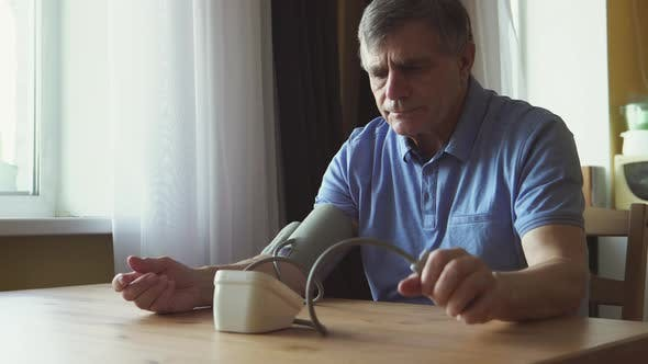 Thumbnail for Elderly man measuring the blood pressure at the room