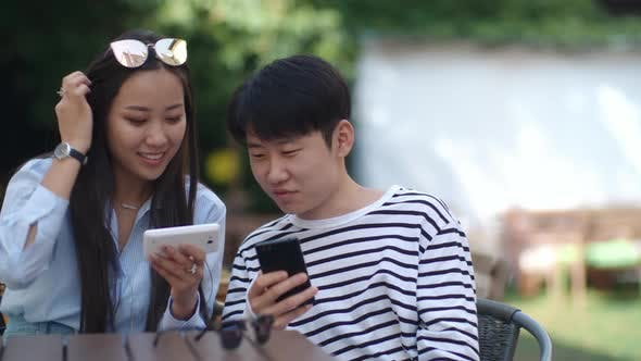 Cover Image for Asian Teens Using Gadgets in Outdoor Cafe