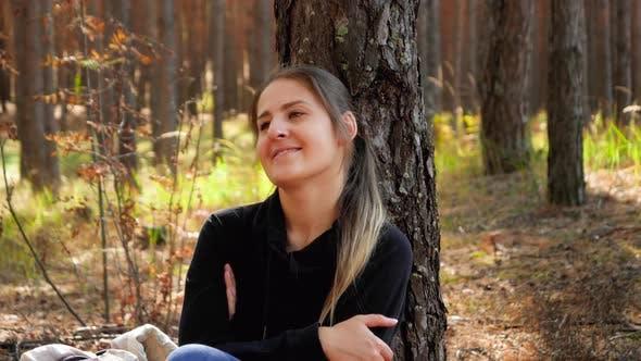Video von Schöne Lächelnde Frau entspannt während Sitzen auf dem Boden im Wald oder Park und lehnte