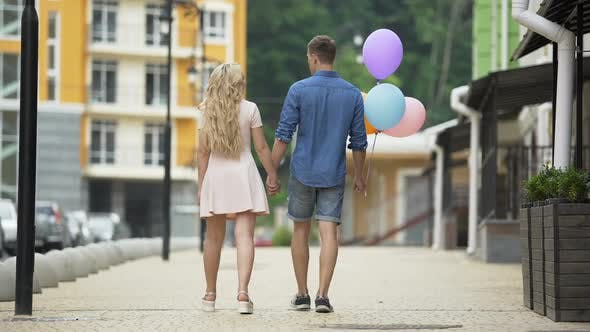 Thumbnail for Couple Walking Down Street Holding Hands Stopping to Kiss Guy with Balloons