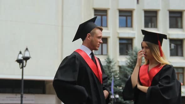 Cover Image for Young Woman and Man in Mantles and Caps Discussing Future, Graduation Day
