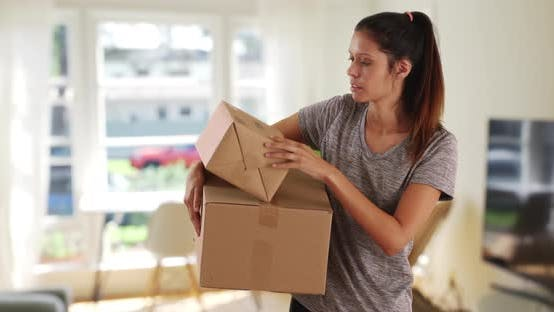 Thumbnail for Beautiful Caucasian woman at home carrying shipping boxes