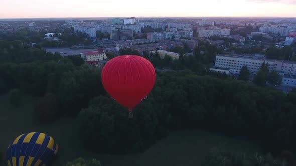 Thumbnail for Red Hot Air Balloon Floating Over City Green Area at Dawn, Festival Early Flight