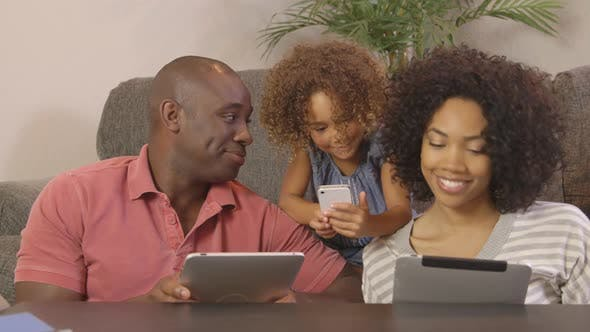 Thumbnail for African American family using cellphone and tablets