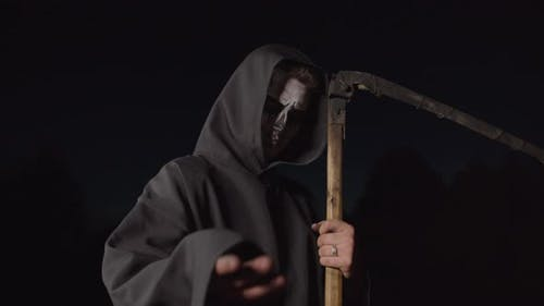 Grim Reaper with Scythe Gesturing To Follow at Dusk