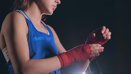 Thumbnail for Close-up of a Beautiful Athletic Female Boxer Pulls Red Bandages on the Hands of a Female Fighter