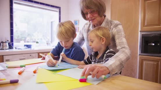 Cover Image for Elderly grandmother teaching children to draw