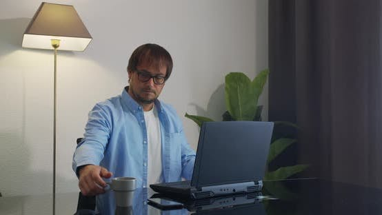 Thumbnail for Businessman in Eyeglasses with Laptop Computer Drinking Coffee or Tea at Office. Business, People