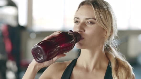 Thumbnail for Thirsty Woman Enjoying Water After Fitness Training in Gym