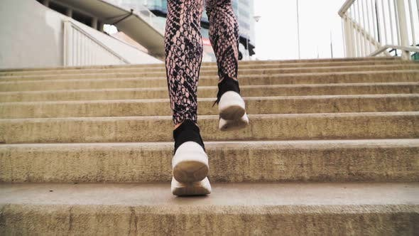 girl runs up the stairs . She is wearing black athletic sneakers and leggings
