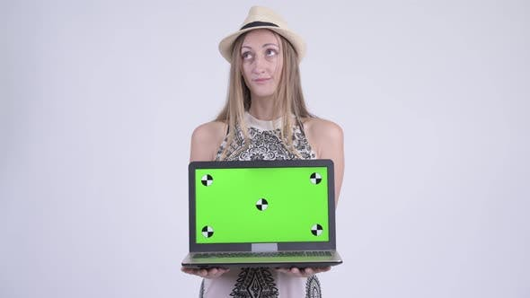 Thumbnail for Portrait of Happy Blonde Tourist Woman Thinking While Showing Laptop