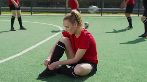 Female Soccer Player Sitting on Field and Tying Shoelaces