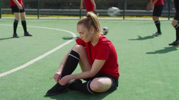 Female Fußballspielerin sitzt auf dem Feld und binde Schnürsenkel