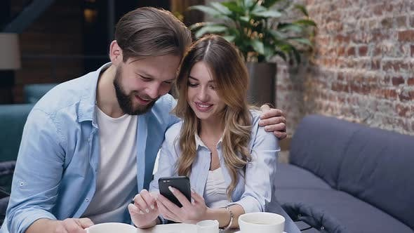 Thumbnail for Young Couple Hugging and Watching at Woman's Phone while Sitting at the Table in Hotel Lobby