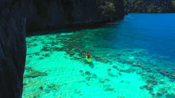 Thumbnail for Aerial View Flying Over Amazing Rocks and Tropical Coral Reef Lagoon. Man and Woman Kayak Are