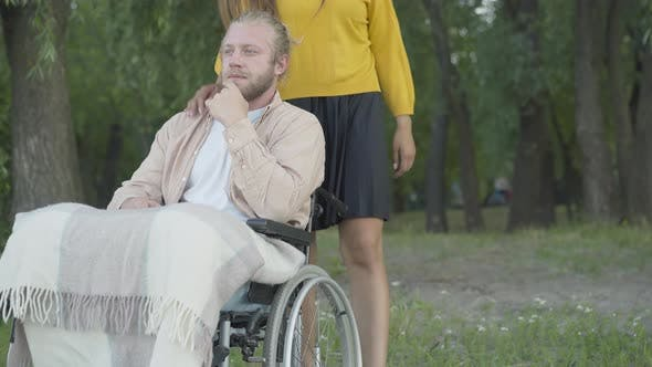 Thumbnail for Unrecognizable Woman Coming To Man Sitting on Wheelchair and Hugging Boyfriend. Portrait of Happy