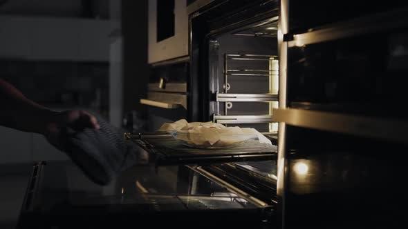 Chef legt Brötchen mit Speck und Huhn in den Ofen zum Braten, Kochen von Fleisch in den Ofen