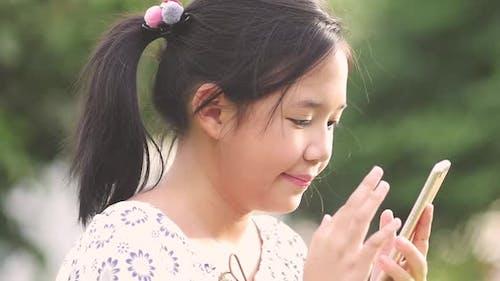 Asiatisches Mädchen mit dem Smartphone