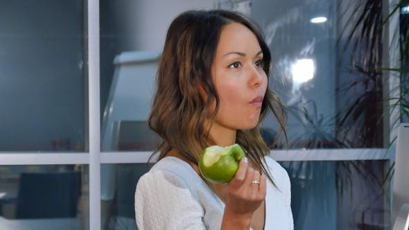 Cover Image for Pretty businesswoman eating green apple in the office
