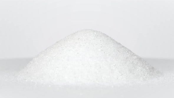 Pile of white sugar rotating on white background