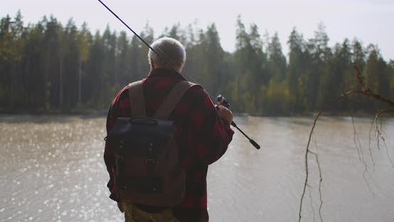 Thumbnail for Fisher Is Viewing Lake in Forest, Choosing Place for Fishing and Enjoying Nature in Autumn Season