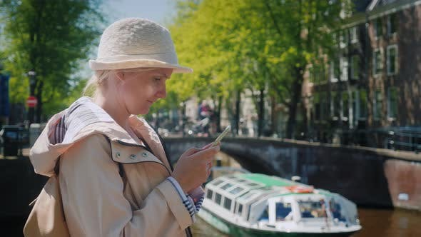 Thumbnail for An Attractive Woman Uses a Smartphone Near One of the Beautiful Canals in Amsterdam. Tourism in the