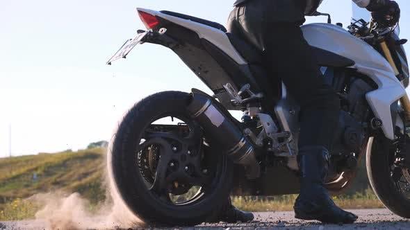 Колесо спортивного мотоцикла начинает вращать на асфальте и поднимать гальки и грязь. Байкер