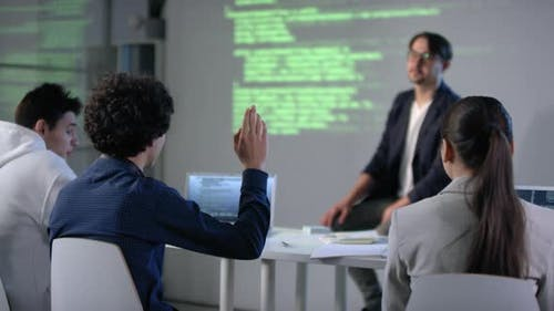 Male Student Raising Hand At IT Class